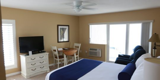 Dresser with TV on the left wall. Dining room table with two chairs on left wall. Patio doors leading to balcony on the center wall. Two recliners and one queen bed along the right wall.